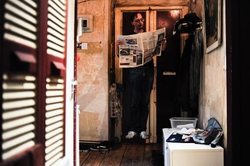Zeitung lesender Mann schwebt über dem Boden